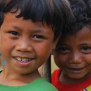 To små gutter står tett og smiler inn i kamera.