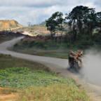 En tømmerbil kjører gjennom et avskoget område.