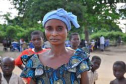 Kvinne i landsby i Kongo med blå kjole og blått hodetørkle