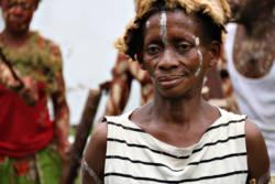 Kvinne fra Kasai-Occidental i Kongo med ansiktsmaling og pelslue