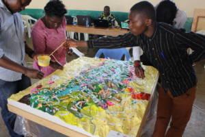 Tre personer maler detaljer på et 3D-kart i plast som ligger på et bord.