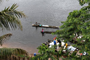 Kongofloden er verdens nest største elv og slynger seg gjennom Sentral-Afrika der den gir vann og liv til regnskogen. På dette bildet ser vi en kvinne som padler i en kano på elva.