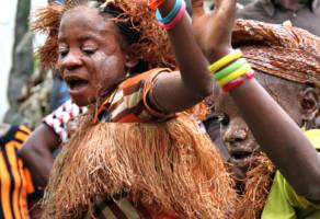 To urfolkskvinner i tradisjonelle klær danser.