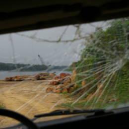 Utsikt gjennom en knust bilrute mot tømmer ved en elv