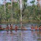 barn i kano i elv med regnskog i bakgrunnen