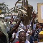 """Pygmeer som demonstrerer. En holder opp skilt hvor det står: """"Loi Dignite Vie!"""""""
