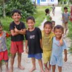 Fem gutter som står ved siden av hverandre og smiler