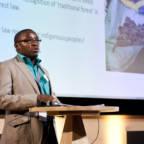 Alphonse Muhindo står på en scene og holder foredrag.