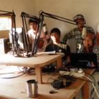 Fem tenåringer som sitter ved mikrofoner