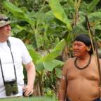 Kong Harald og Davi Kopenawa står ved siden av hverandre, med regnskogen i bakgrunnen. Davi holder en pil og en bue.