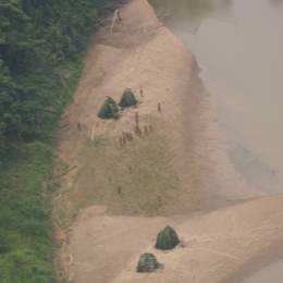 Flyfoto av isolerte indianere på en elvebredd.
