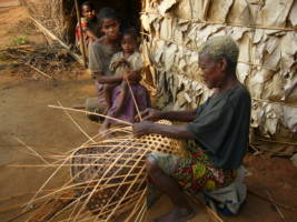 En eldre kvinne i Kongo sitter på bakken og fletter en kurv.