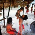 En ung Waiapi-indianer løfter en baby opp i lufta. Mora sitter ved siden av dem.