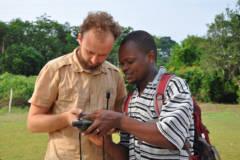 Regnskogfondet-ansatt står sammen med en innbygger i en kongolesisk landsby og ser på et GPS-apparat.