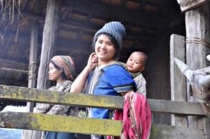 to kvinner, en av dem med en baby på armen, smiler mot kamera utenfor en hus i landsbyen Hlo Lang Pan i Myanmar.