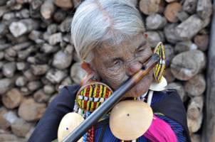 En eldre kvinne spiller fløyte med nesen.