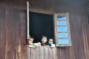 Tre små barn kikker ut av et vindu.