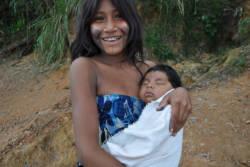 Smilende Panara-jente med baby på armen